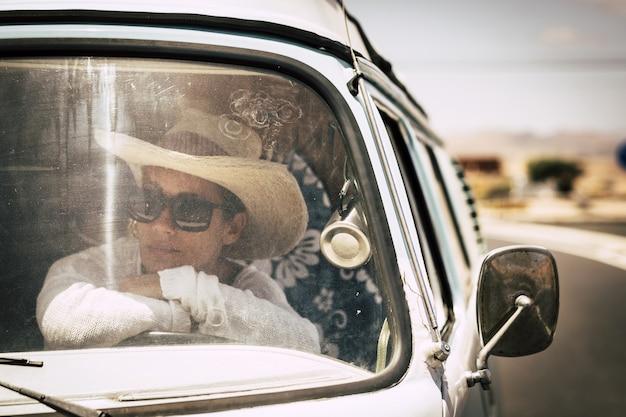 Concept de voyage avec une belle femme adulte caucasienne indépendante conduisant une vieille camionnette vintage