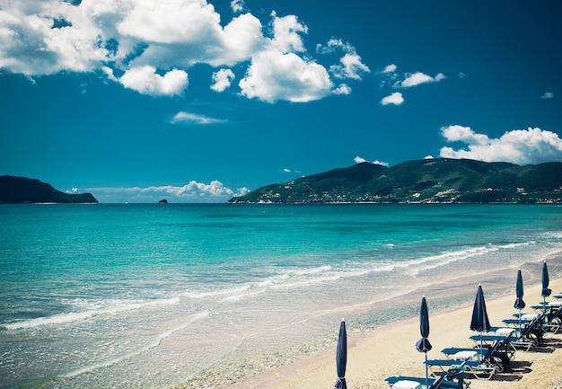 Concept de voyage - chaises longues avec parasols sur la belle plage, île de zakynthos, grèce