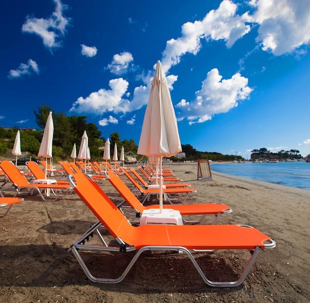 Concept de voyage - chaises longues avec parasols sur la belle plage, l'île de zakynthos, grèce