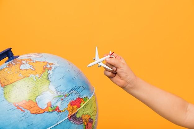 Concept de voyage. childs hands holding figurine d'avion de passagers. avion volant vers le globe.