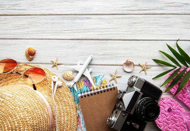 Concept de voyage d'été. ancien appareil photo argentique, chapeau, coquille et feuilles de palmier sur une table en bois blanc.
