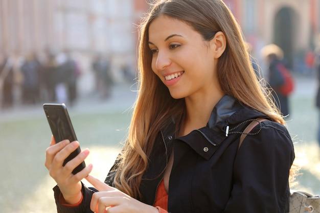 Concept de voyage. femme belle jeune voyageur à l'aide de la carte d'application sur téléphone intelligent. fille de touriste explorant la ville avec sac à dos et téléphone portable.