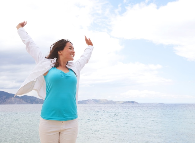 Concept de voyage - fille heureuse sautant sur la plage, vacances d'été.