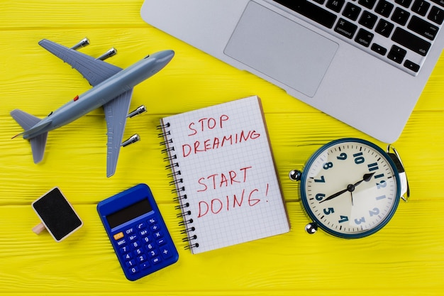 Concept de voyage et de finance à plat. arrêtez de rêver, commencez à faire. avion, calculatrice, réveil et ordinateur portable.