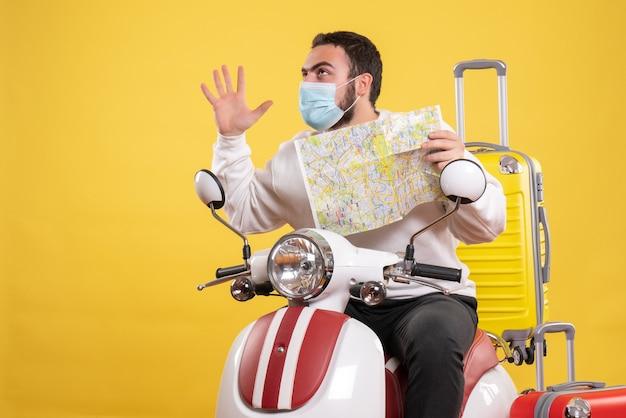 Concept de voyage avec un gars confiant dans un masque médical assis sur une moto avec une valise jaune dessus
