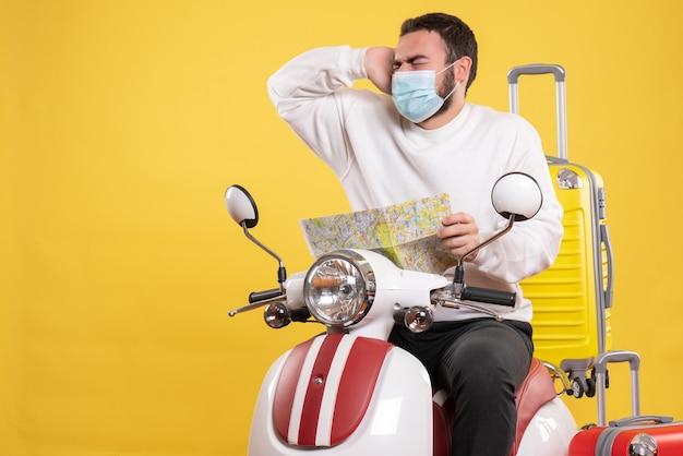 Concept de voyage avec un gars émotif en masque médical assis sur une moto avec une valise jaune dessus
