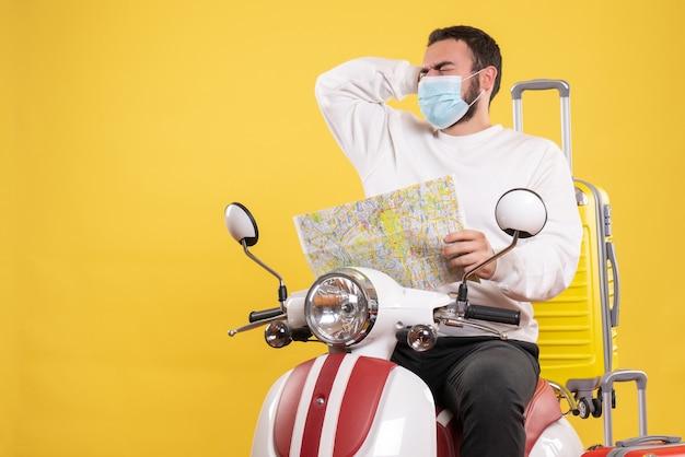 Concept de voyage avec un gars troublé dans un masque médical assis sur une moto avec une valise jaune dessus