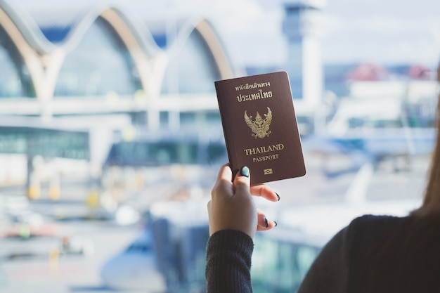Concept de voyage. gros plan d'une main de femme détenteur d'un passeport thaïlandais prêt à embarquer.