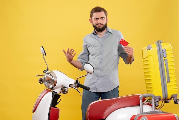 Concept de voyage avec jeune homme ambitieux debout derrière la moto et tenant la carte bancaire sur jaune