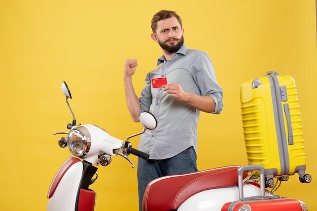Concept de voyage avec un jeune homme ambitieux debout derrière une moto avec des valises sur elle et tenant une carte bancaire sur jaune