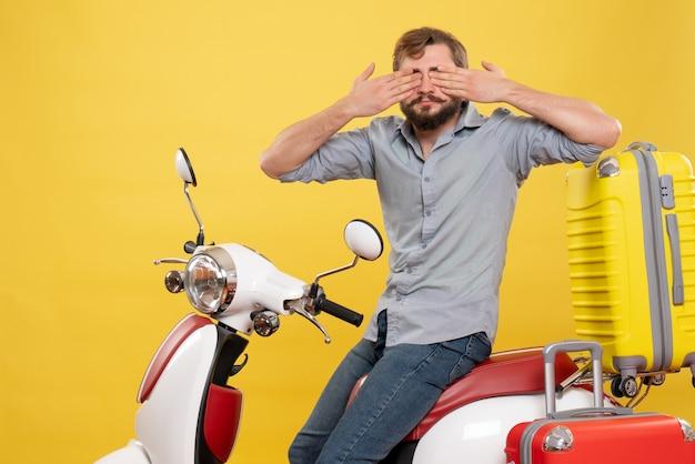 Concept de voyage avec jeune homme barbu assis sur une moto et fermant les yeux dessus sur jaune