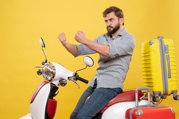 Concept de voyage avec jeune homme barbu en colère émotionnelle assis sur la moto sur elle sur jaune