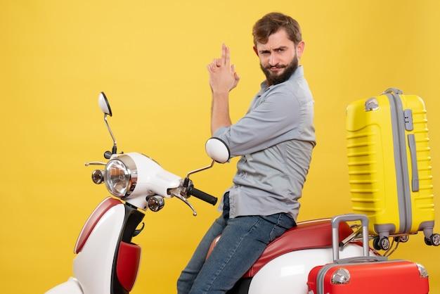 Concept de voyage avec jeune homme barbu confiant assis sur la moto sur elle faisant le geste des armes à feu sur jaune