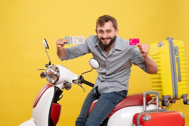Concept de voyage avec jeune homme barbu confiant assis sur une moto tenant une carte bancaire et un billet sur elle sur jaune