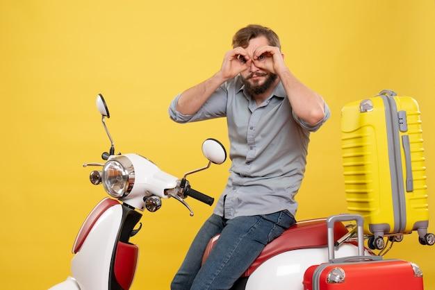 Concept de voyage avec jeune homme barbu émotionnel assis sur la moto sur elle faisant le geste de lunettes sur jaune
