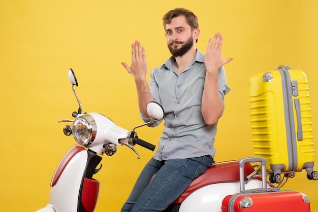 Concept de voyage avec jeune homme barbu émotionnel assis sur la moto sur elle montrant les mains sur le jaune