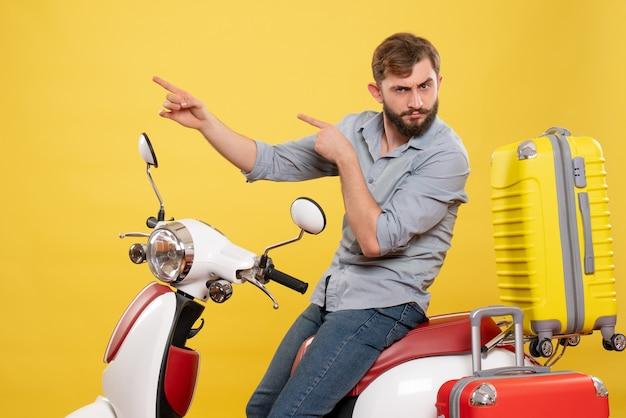 Concept de voyage avec jeune homme barbu émotionnel assis sur une moto sur elle pointant vers le haut sur jaune