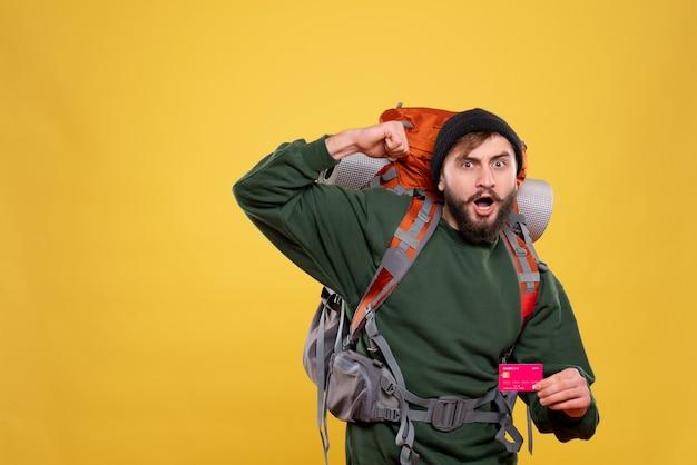 Concept de voyage avec un jeune homme fier et ambitieux avec packpack et tenant une carte bancaire sur jaune