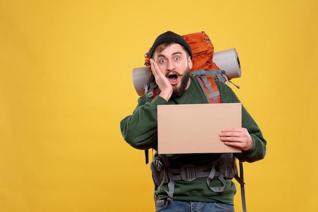 Concept de voyage avec jeune homme surpris avec packpack et tenant une feuille sans écrire dessus sur jaune
