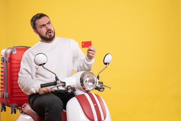 Concept de voyage avec un jeune homme de voyage confus assis sur une moto avec une valise dessus tenant une carte bancaire sur jaune