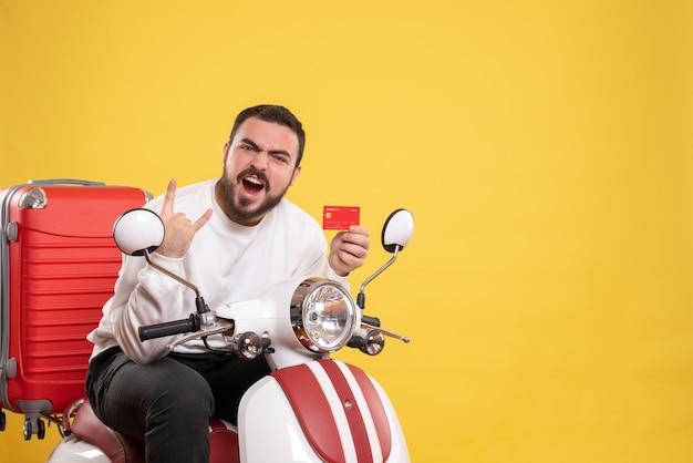 Concept de voyage avec un jeune homme de voyage drôle et émotionnel fou assis sur une moto avec une valise dessus tenant une carte bancaire sur jaune