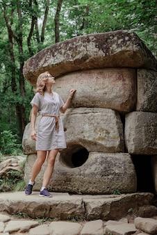 Concept de voyage et de liberté. jeune femme en robe d'été marchant près de grosse pierre de dolmen dans la forêt