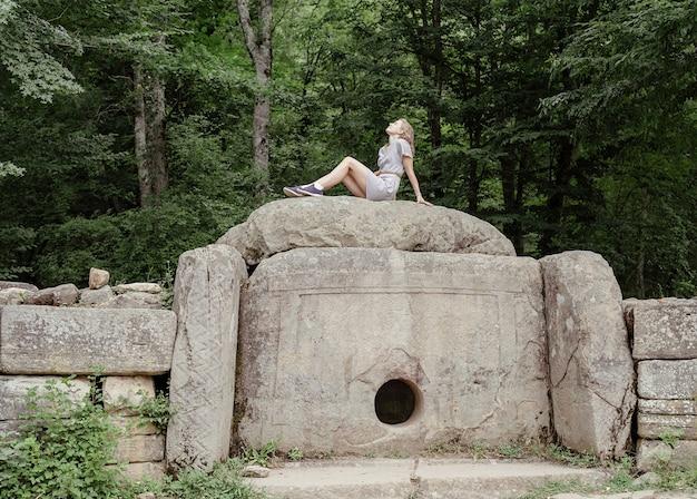 Concept de voyage et de liberté. vue arrière d'une jeune femme en robe d'été assise
