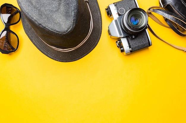 Concept de voyage avec des lunettes de soleil et un chapeau de valise de films de caméra rétro sur jaune