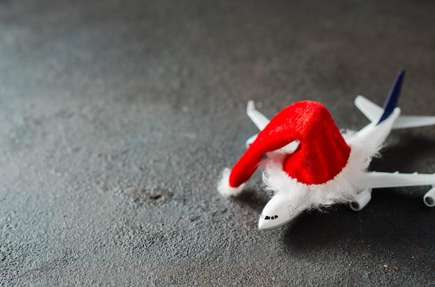 Concept de voyage de noël ou du nouvel an. avion jouet et chapeau de père noël.