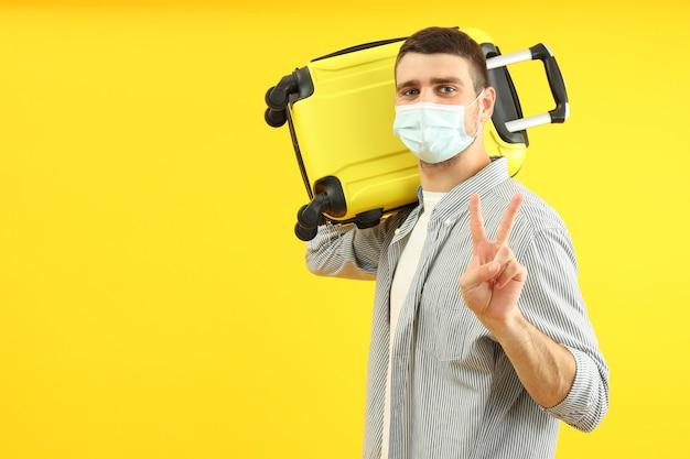 Concept de voyage pendant le coronavirus avec un jeune homme sur fond jaune.
