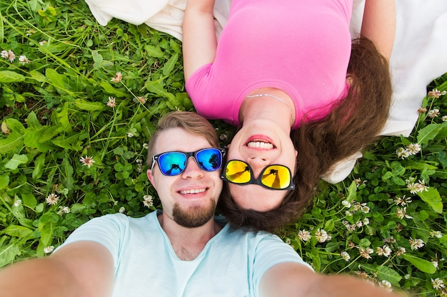 Concept de voyage, de relation et de personnes - beau couple charmant regardant la caméra en prenant selfie