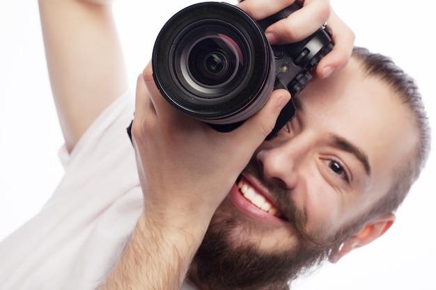 Concept de voyage, de technologie et de style de vie : jeune photographe barbu prenant des photos avec un appareil photo numérique