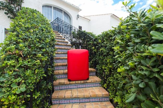 Concept de voyage, de tourisme et d'accessoires - valise rouge debout sur les escaliers et prête à voyager.