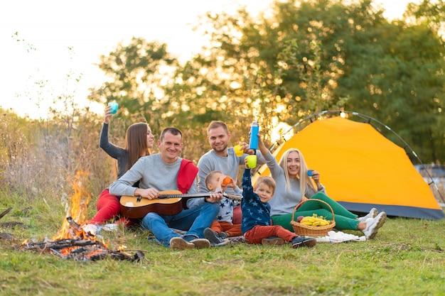 Concept de voyage, tourisme, randonnée, pique-nique et personnes - groupe d'amis heureux avec tente et boissons jouant de la guitare au camping