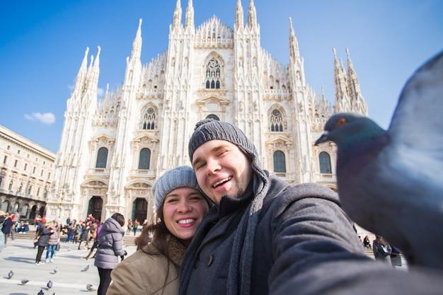 Concept de voyage et de vacances d'hiver - touristes heureux prenant un autoportrait avec de drôles de pigeons devant la cathédrale duomo à milan
