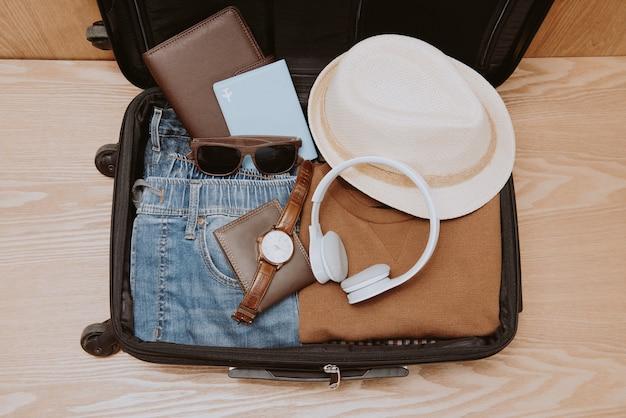 Concept de voyage et de vacances. sac de voyage ouvert avec vêtements, accessoires, carte de crédit, billets et passeport.