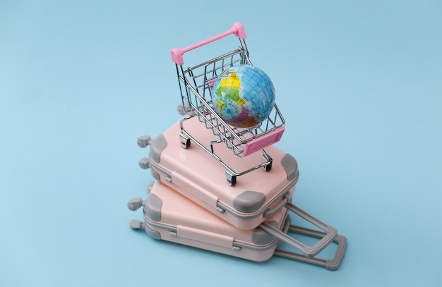 Concept de voyage, de vacances ou de tourisme. deux mini valises de voyage et caddie avec globe sur fond bleu