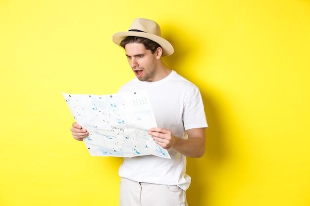 Concept de voyage, de vacances et de tourisme. touriste semblant mécontent et choqué par la feuille de route, debout sur fond jaune
