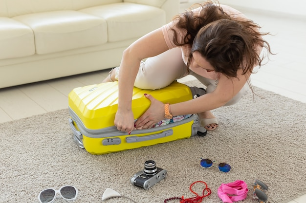 Concept de voyage, voyage et vacances - femme essayant de fermer sa valise