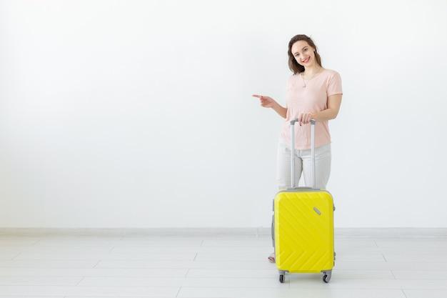 Concept de voyage, voyage et vacances - femme avec son point de valise jaune sur l'espace de copie