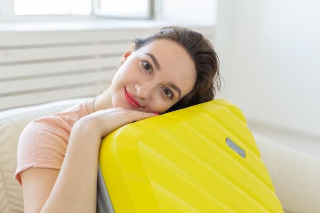 Concept de voyage, voyage et vacances - jeune femme serrant sa valise jaune