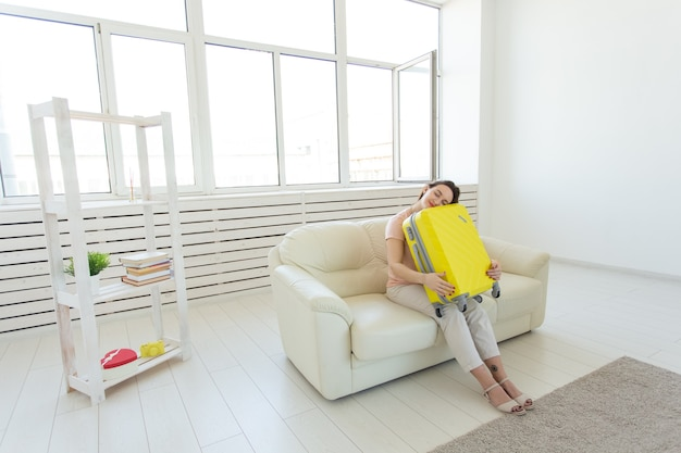 Concept de voyage, voyage et vacances jeune femme serrant sa valise jaune
