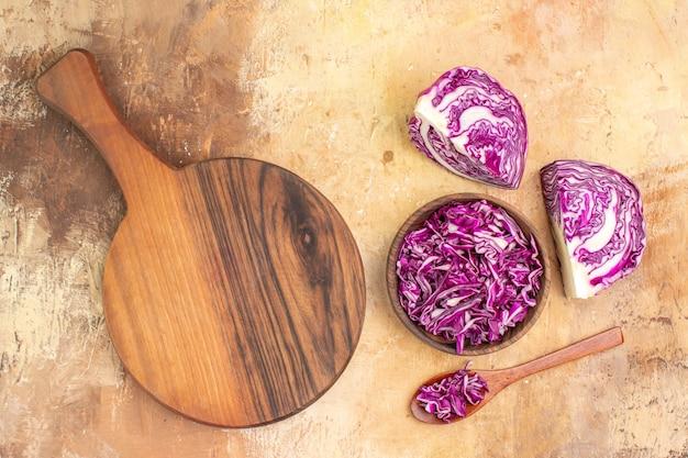 Concept de vue de dessus avec un bol de chou rouge haché et une planche à découper pour faire de la salade de betteraves sur un fond en bois avec lieu de copie