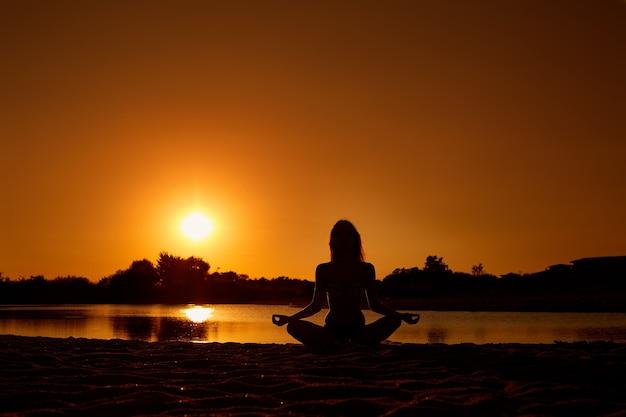 Le concept de yoga harmonie méditation santé silhouette d'une jeune fille en position du lotus