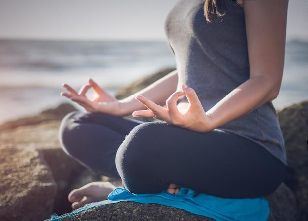 Concept de yoga main de femme pratiquant la pose de lotus sur la plage
