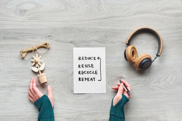Concept zéro consommation consciente des déchets à plat, vue de dessus des mains tenant une fleur en bois à la mode, cahier en moleskine avec couvercle en carton artisanal, lunettes de lecture et écouteurs sur table en bois