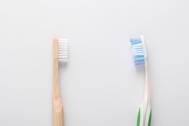 Concept zéro déchet, brosse à dents en bois eco vs brosse à dents en plastique sur fond blanc: