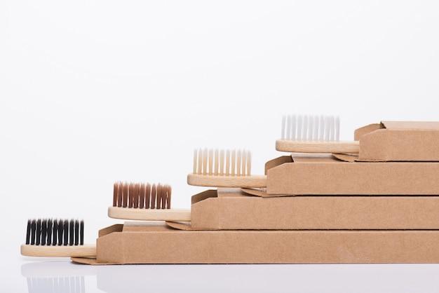 Concept zéro déchet. close-up macro vue de profil côté photo de brosses à dents écologiques dans l'emballage isolé sur fond blanc