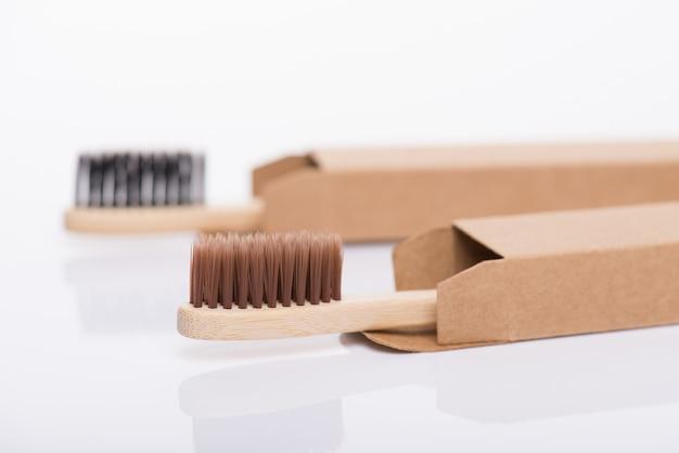 Concept zéro déchet. close-up side view photo de l'éco-responsable enveloppé dans du carton de l'artisanat couvercle du boîtier de la boîte des brosses à dents noires et brunes isolées sur fond blanc