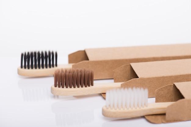 Concept zéro déchet. gros plan, vue de profil, photo de l'environnement, emballé dans du papier, emballage en carton recyclé, noir, brun et blanc, brosses à dents isolées sur fond blanc
